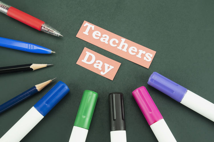 High angle view of teachers day text with multi colored writing instrument on table