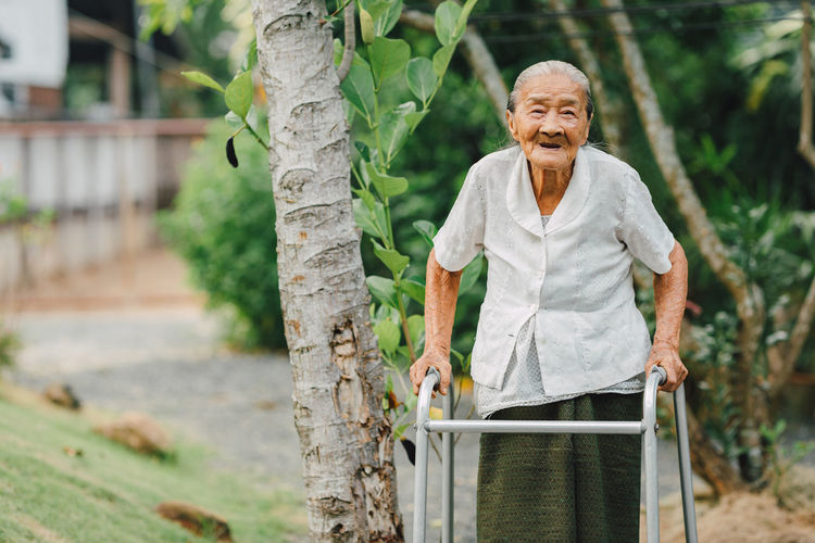 Healthy eldery people walking with walker as adaptive device for fall prevention.