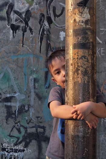 Portrait Of Boy Embracing Metallic Rod
