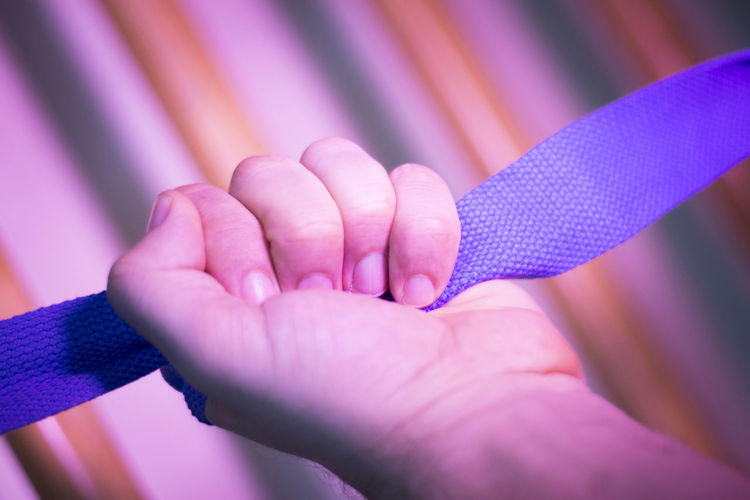 Cropped hand holding strap in gym