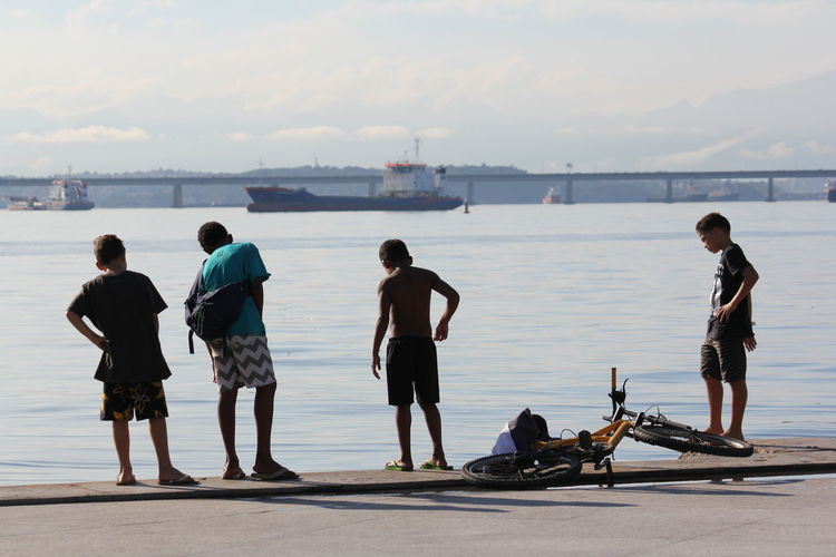 Brazil Rio De Janeiro Boys Boys Playing Casual Clothing Child Full Length Group Of People Leisure Activity Lifestyles Males  Nature Outdoors People Real People Rear View Sea Sky Street Photography Togetherness Transportation Water Women Adventures In The City