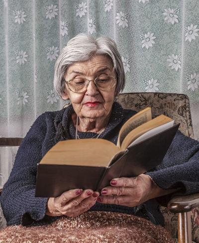 Portrait of an old woman reading a book. Learning Novels Reading Book Close-up Culture Elderly Elderly Woman Expression Eyeglasses  Grandmother Gray Hair Indoors  Lifestyles Literature One Person One Senior Woman Only Pensioner Portrait Reading A Book Real People Retirement Senior Adult Senior Women Sitting
