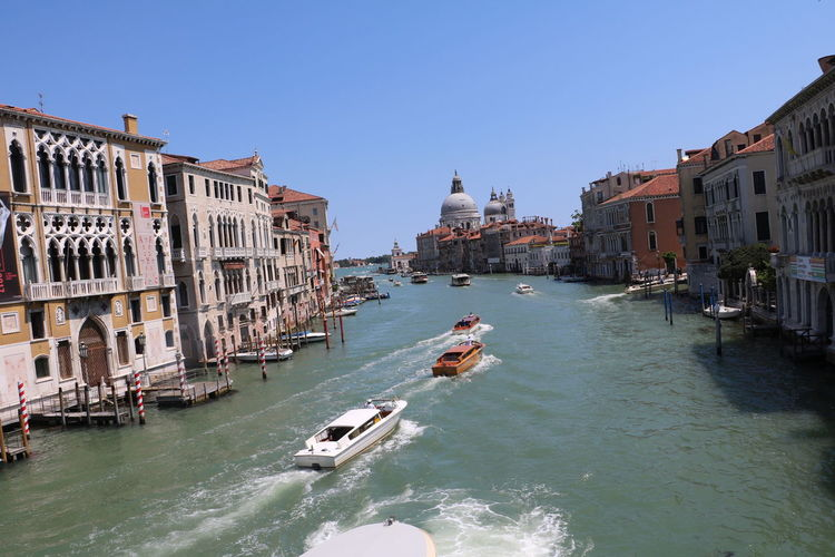 Boats speeding through one of the canals in Venice, Italy. Architecture Docked Grand Canal Narrow Speeding Travel Adriatic Sea Archiac Blue Boat Building Canal Clean Clear Curved  Docks Dome Europe Italy Old Sky Speed Boats Structure Venice Water