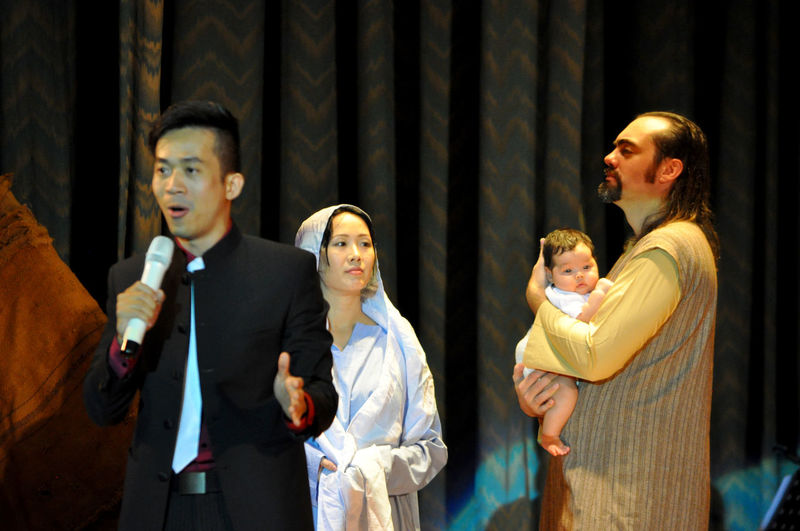 Singer in front of live nativity scene during Christmas concert in Da Nang theatre, Vietnam. Actors Amateurs Babies Baby Jesus Christmas Concerts Costumes Danang Events Joseph Mary Nativity Performers Singers Stage Show Stages Theaters Theatres  Vietnam Vocalists