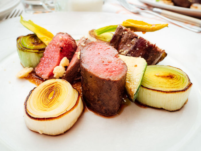 Close-up of roasted lamb and leek served in plate