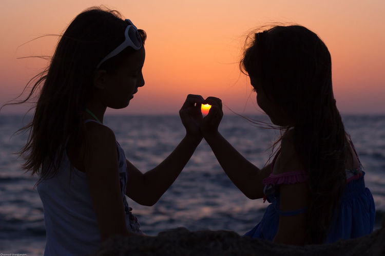 Girls Making Heart Shape With Hands While Sitting At Sea Shore During Sunset