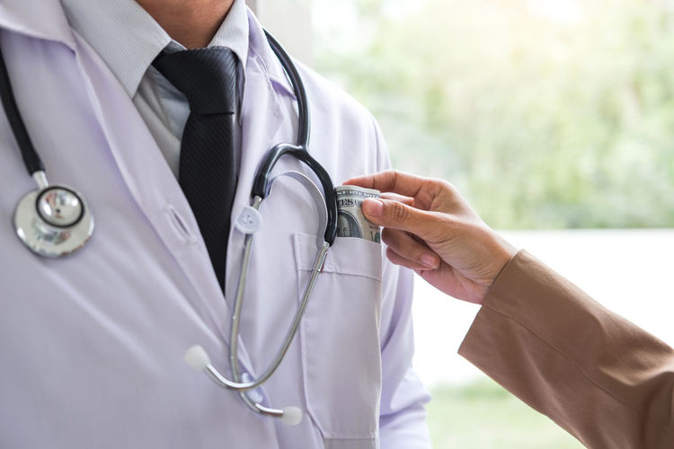 Cropped image of woman bribing doctor wearing stethoscope