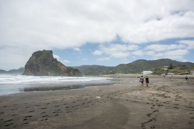 Auckland, New Zealand-December 17,2016: Tourists exploring the black sand Piha Beach on an overcast day in Auckland, New Zealand Auckland Lion Rock Tasman Sea Beach Black Sand Beach Coast Famous Place Group Of People Land Mountain Mountain Range Nature New Zealand Piha Real People Sand Scenics - Nature Sea Shore Togetherness Travel Destinations Volcanic Crater Volcanic Landscape Walking Water