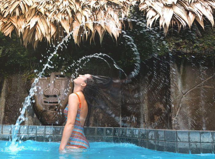 Side view of woman tossing wet hair in swimming pool