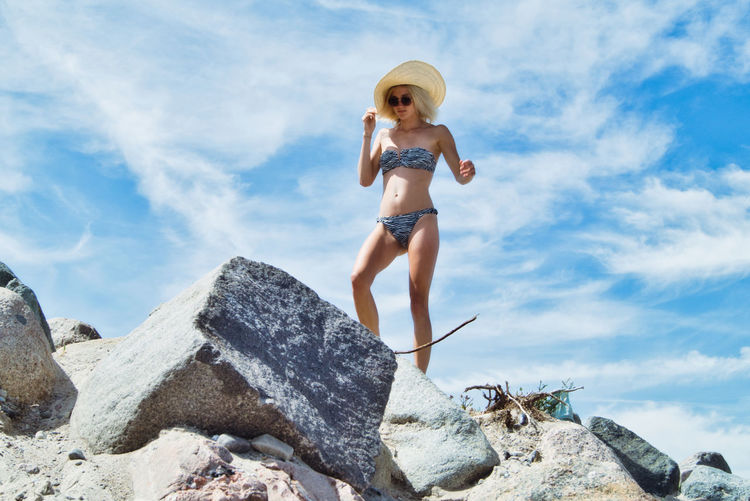 Low angle view of young woman in bikini walking on rock against sky