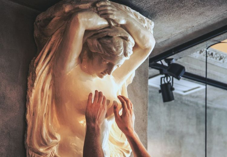 Cropped Hands Of Man Touching Female Statue Breast