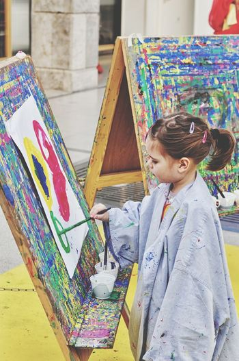 Girl painting on canvas at art studio