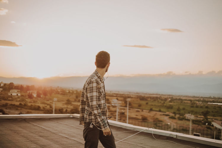 Man Standing On Terrace Against Sky During Sunset