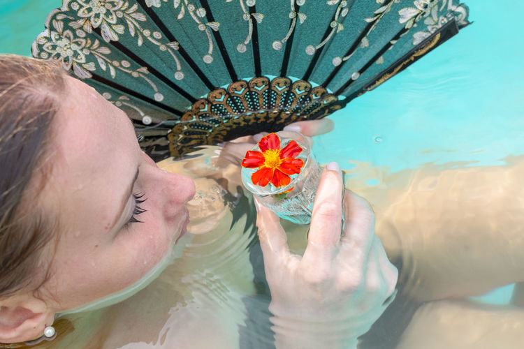 High angle view of woman holding hand fan and wineglass while in swimming pool