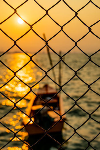 Mesh Wire Fence Silhouette Blurred Background Fishing Boat Morning Sun Sunrise Sunset Sea Sunshine Offshore Yellow Outdoors Water Sky