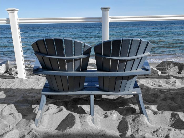 Chairs on beach against sky