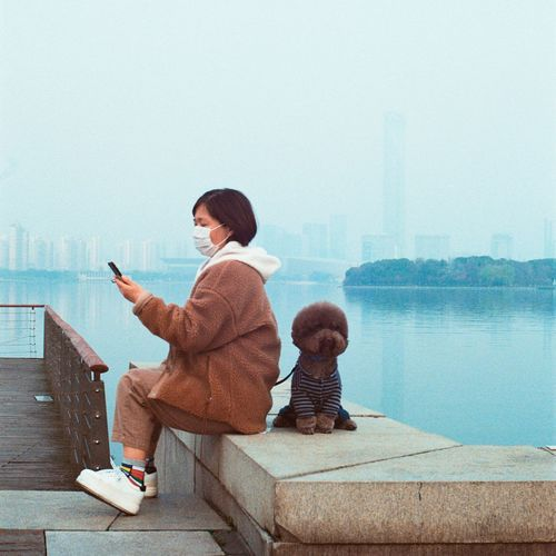 Rear view of woman sitting on mobile phone against sky