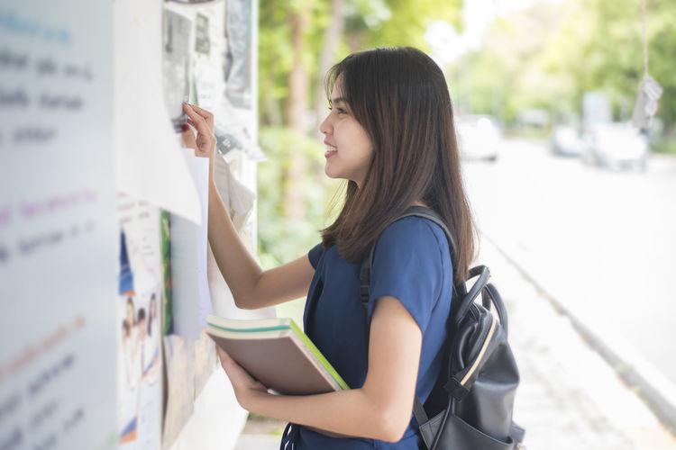 Young woman looking at bulletin board