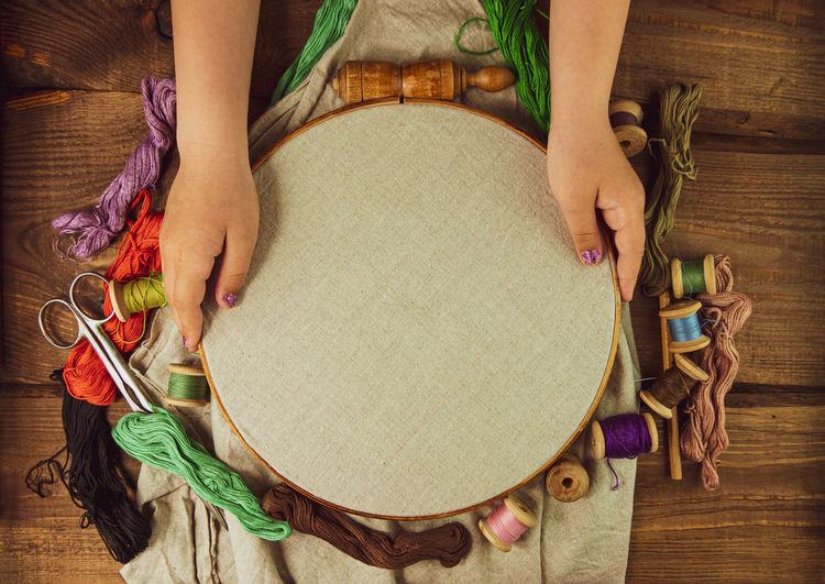 Embroidery needlework background linen hoop. colorful floss thread scissors card tag  hands handmade