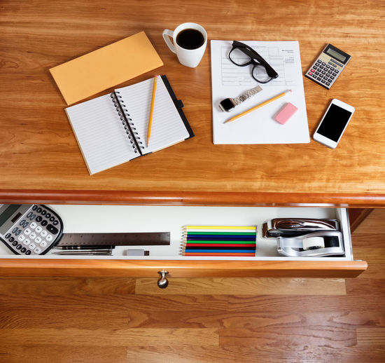 Overhead view of solid cherry desktop with personal income forms and office supplies Business Cherry Wood Coffee Desktop IRS Communication Desk Drawer Finance Income Tax Law Paper Pencil Personal Tax Wireless Technology