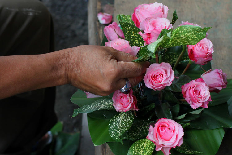 Cropped hand of man touching rose bouquet
