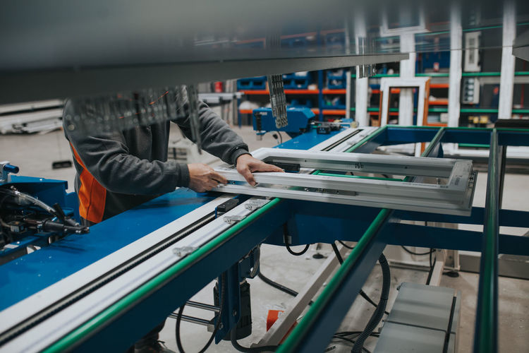 Midsection of manual worker making window frame at factory