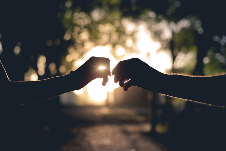 Silhouette of couple's hands outdoors