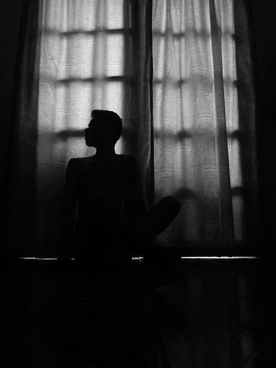 Silhouette woman looking at window in dark room