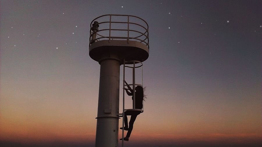 Silhouette Woman Climbing Steps Of Lookout Tower At Night