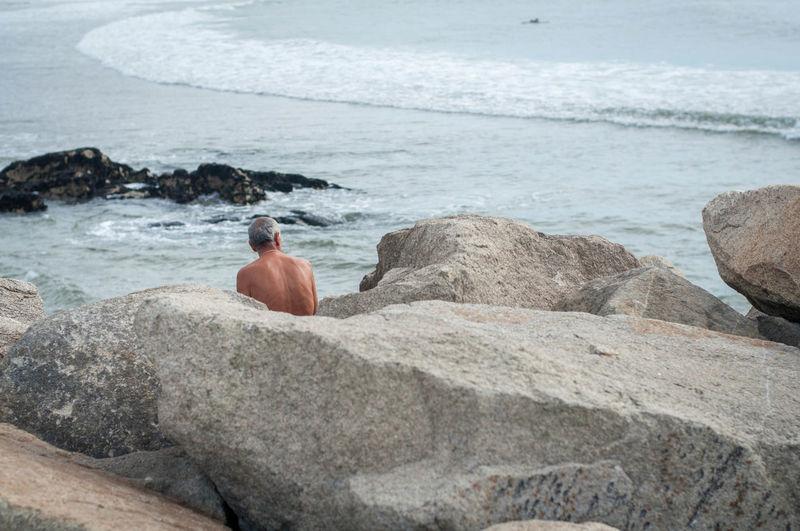 Shirtless man sitting by rocks at beach