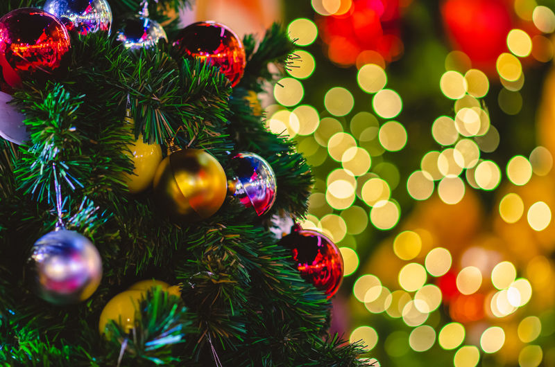 Selective focus of baubles hanging on christmas tree with colorful bokeh background.