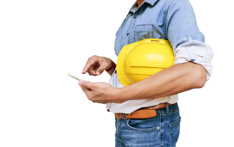 Midsection of architect holding hardhat while using smart phone against white background