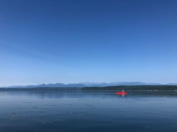 Far off kayaker Nautical Vessel Water Transportation Sky Blue Mode Of Transportation Scenics - Nature Mountain Tranquility No People Travel Nature Day Tranquil Scene Clear Sky Beauty In Nature Outdoors Sea Land Copy Space