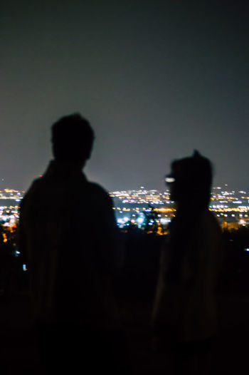 Rear view of silhouette man standing by illuminated city against sky at night