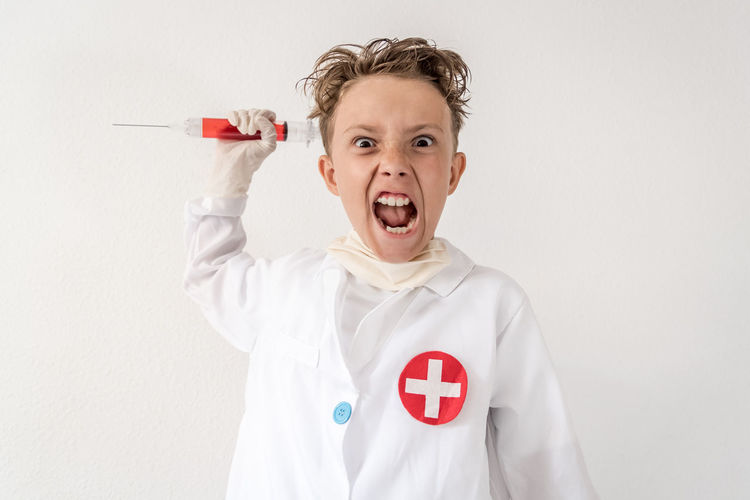 Boy impersonating himself as a scientist. Young child playing as a mad doctor screaming with wide eyes having fun with a bloody syringe. Little boy pretending to be a crazy medic with tousled hair Portrait Indoors  One Person Front View Studio Shot Mouth Mouth Open White Background Emotion Men Looking At Camera Males  Standing Red Childhood Boys Waist Up Casual Clothing