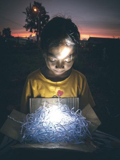 Close-up of girl holding illuminated box at night