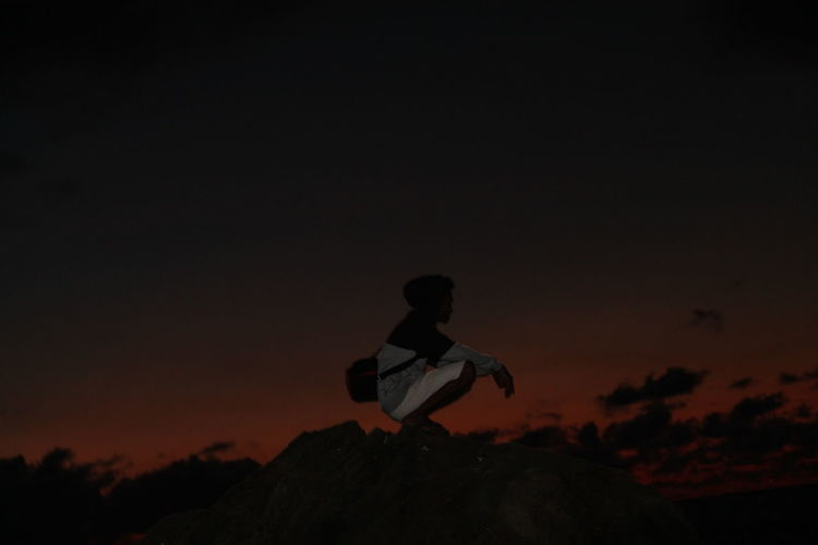 Silhouette man sitting on rock against sky during sunset