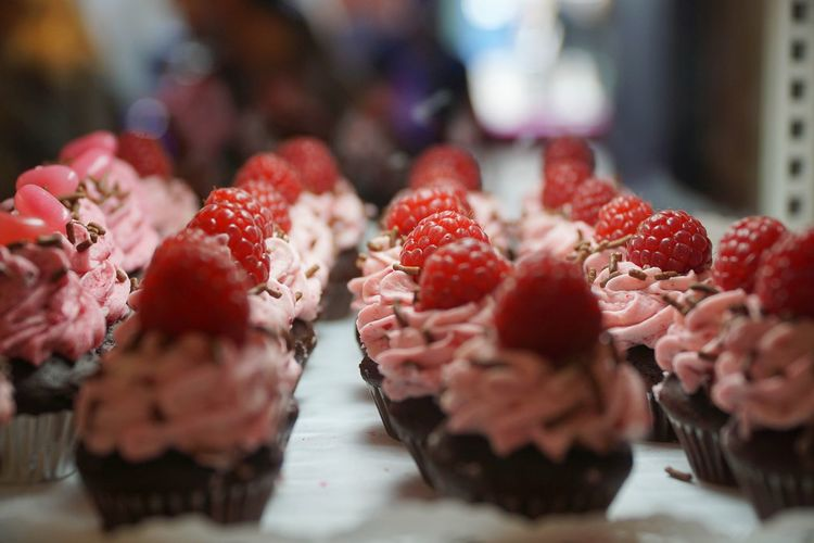 Close-Up Of Muffins With Raspberries Arranged In Row