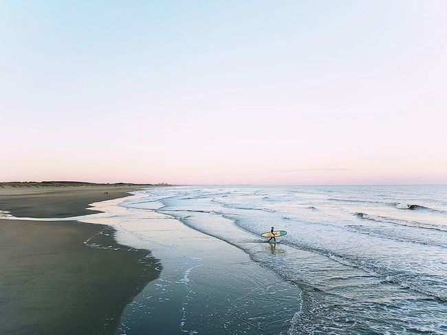 Solitary surfer Sea One Person Outdoors Beach Surfing Clear Sky Horizon Over Water Sky Water Blue Sunlight Natural Outdoor Life Adventure Is Out There Sunrise Sports Adventure Finditliveit Coast Europe Sun