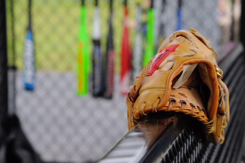 Close-up of baseball gloves on railing