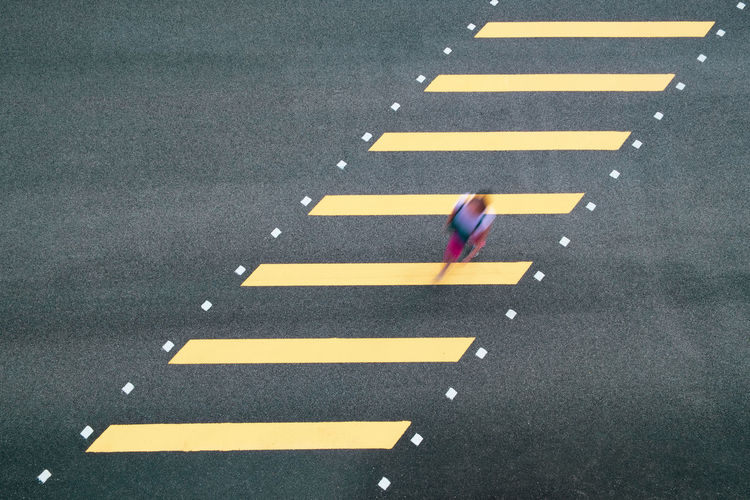 High angle blurred motion of woman walking on zebra crossing