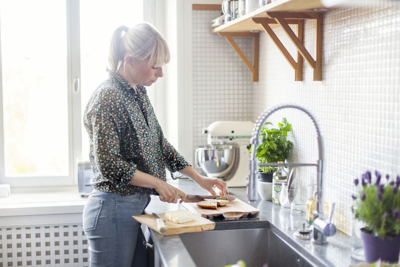 Woman standing in kitchen at home