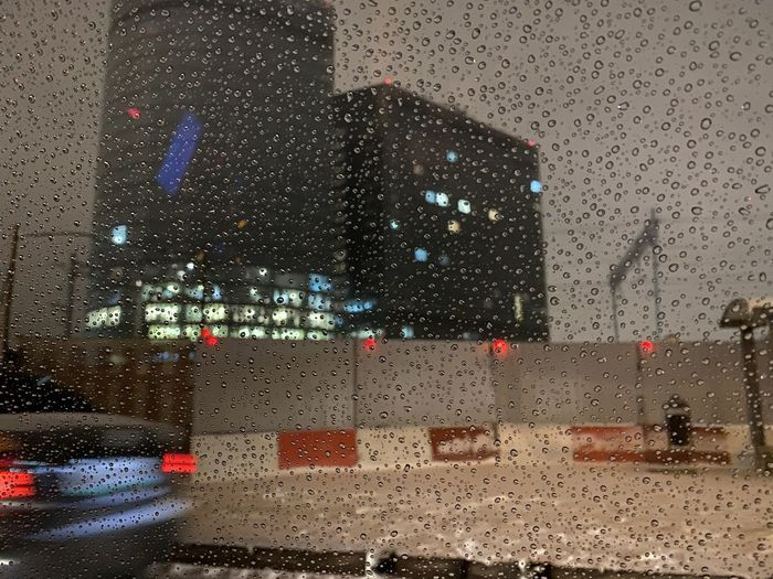 City seen through wet glass during rainy season