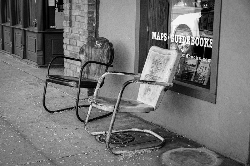 Empty chairs on sidewalk against buildings in city