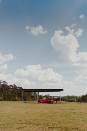 Vintage Red truck in open field Copy Space Farm Farm Life Farmland Isolated Pasture Red Red Truck Beauty In Nature Cloud - Sky Day Field Grass Land Vehicle Landscape Minimalism Nature negative space No People Outdoors Sky Transportation Tree Truck Vintage