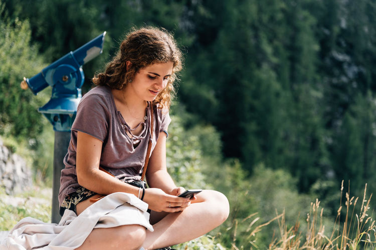 Young Woman Using Mobile Phone While Sitting Against Tree