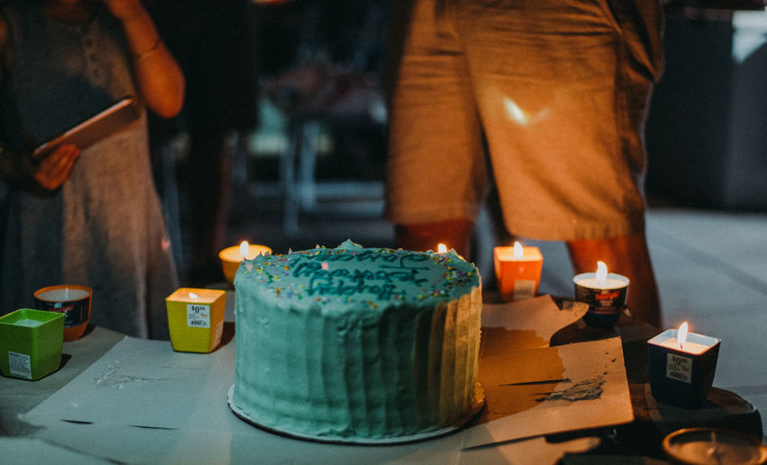 Birthday Party Birthday Cake Candle Birthday Birthday Candles Burning Cake Candle Close-up Container Fire Flame Focus On Foreground Food Food And Drink Illuminated Incidental People Indoors  Lifestyles Men Midsection One Person Real People Sweet Food Table