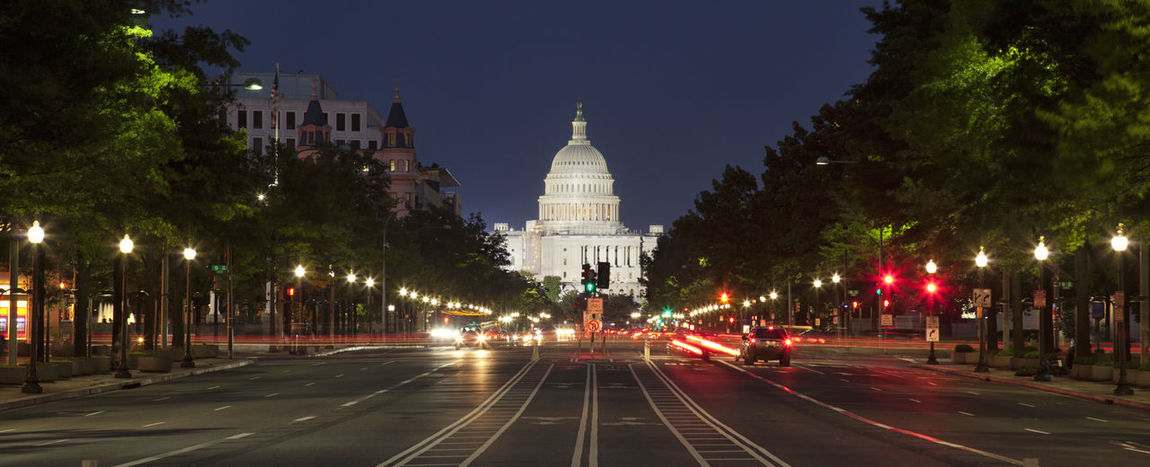 The US Capitol building viewed at night from Constitution Avenue in Washington DC America Architecture Avenue Cars City Constitution Famous Place Government Building Headlights Historical Building Horizontal Lights Maryland Night Photography Storefronts Street Traffic Trees US Capitol Building USA Washington D.C. Washington DC