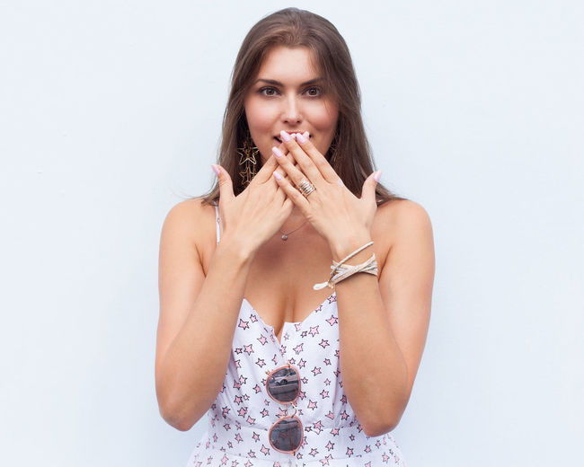 Portrait of beautiful young woman covering mouth with hand against white background