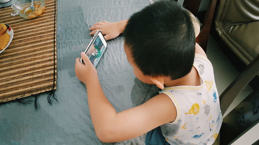 High Angle View Of Boy Using Mobile Phone At Home